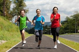 madre con hijos corriendo al aire libre foto