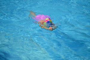niña jugando en la piscina foto