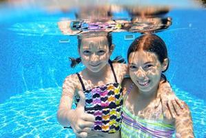Niños felices nadan en la piscina bajo el agua, niñas nadando foto