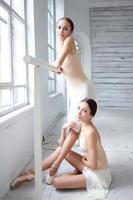 los dos bailarines de ballet clásico posando en barre