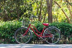 Red bicycle standing in park photo