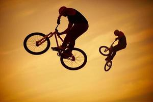 Two men performing BMX tricks on their bikes in the air