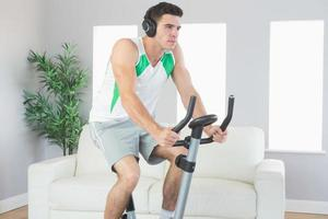 Hombre guapo severo entrenamiento en bicicleta estática escuchando música foto