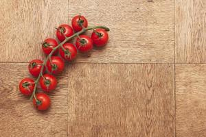 cherry tomatoes on a wooden table, spray