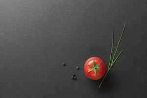 red tomato with green onion on black photo