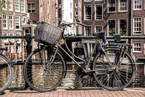 Amsterdam with old bicycles on the bridge against canal, Holland