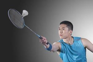 Young man playing badminton, hitting photo