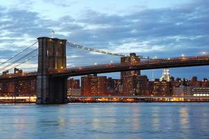 Puente de Brooklyn con el horizonte del centro al atardecer foto