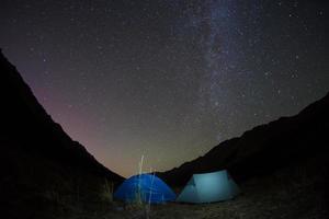 noche acampando bajo las montañas de estrellas