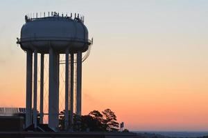 Water tower silhouette at sunrise