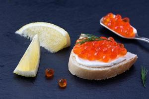 Bread with fresh cream cheese and red caviar photo