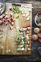 Preparatives for vegetable brochettes camping over a wooden table.