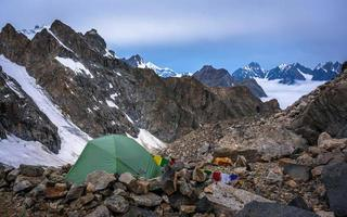 Lonely mountaineers camp in very high snowy moutains beside glacier.