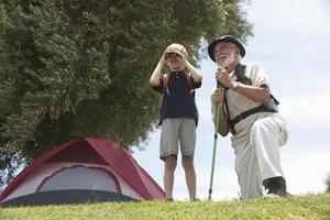 Grandfather and grandson bird watching in front of tent