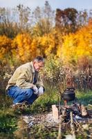 el hombre hierve caldera hollín en el fuego foto