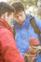 mannelijke wandelaars kijken naar touw in het bos