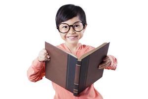 Cute child reading book in studio photo