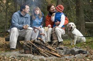 Happy family with dog near campfire photo
