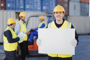 Worker holding sheet in shipping yard photo