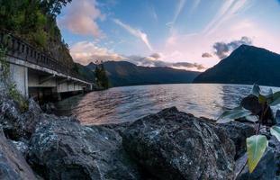 puesta de sol en las rocas junto al puente sobre el lago creciente