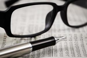 closeup glasses on financial newspaper