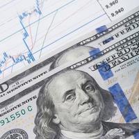 Hundred US dollars banknote over stock graph - studio shot photo