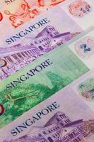 notas diferentes de Singapura em cima da mesa
