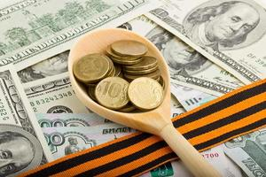Wooden spoon with coins on a background of money photo