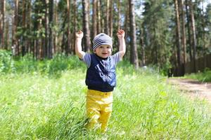 lovely baby walking in forest against flowers