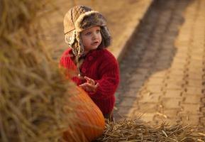 Small girl picking big pumpkin