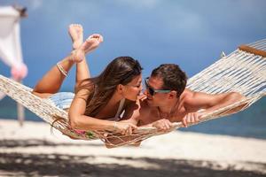 Pareja romántica relajante en hamaca de playa