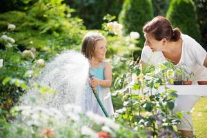 Girl and granny watering flowers in garden