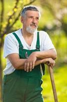 portret van een knappe senior man tuinieren