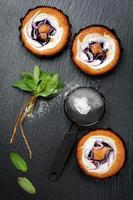Blueberry tarts with fresh mint.Background chalk board
