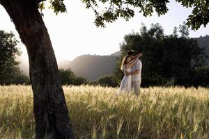Couple hugging in rural field