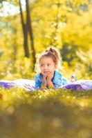 Happy smiling little girl laying in a meadow