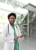 Male Indian healthcare worker wearing a green Scrubs.
