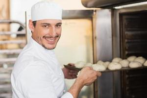 Smiling baker putting dough in oven photo