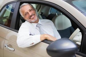 Smiling businessman sitting at wheel of a car