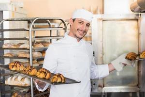 sonriente panadero con bandejas de cruasanes