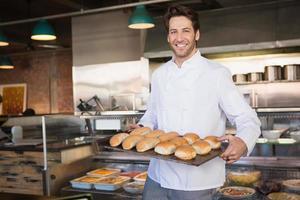 feliz panadero mostrando bandeja con pan foto