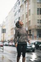 Fitness mujer joven expuesta a la lluvia mientras trota al aire libre foto