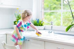 Cute curly toddler girl washing dishes, cleaning with sponge photo
