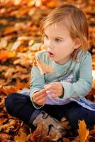 Baby girl on an autumn background photo