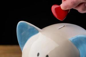 Hand putting heart in piggy bank