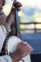 Young man playing banjo outdoors in daylight photo