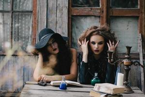 Two vintage witches perform magic ritual photo