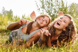 two girlfriends lying down on grass photo