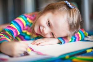 Little cute girl painting with pencils photo
