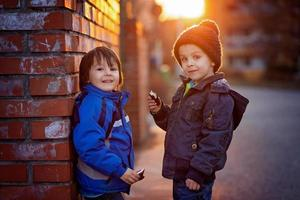 Two adorable little boys, next to brick wall, eating chocolate